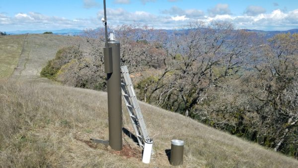Tall metal rain gauge with metal ladder leaning against it on grassy hillside with oaks and mountains in background.