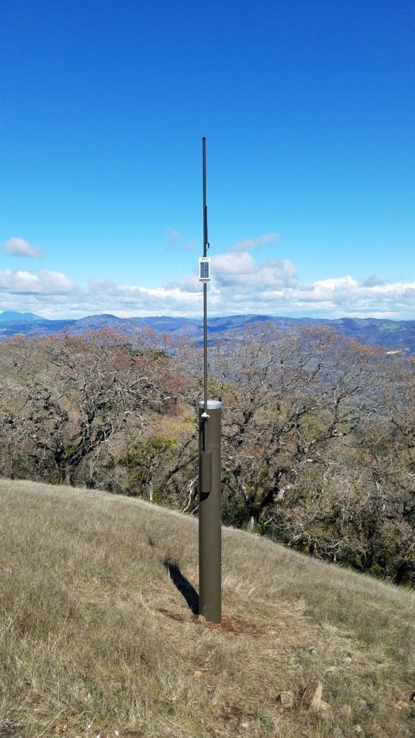 Vertical shot of tall metal rain gauge on grassy hillside with oaks in the background and mountains in the distance.