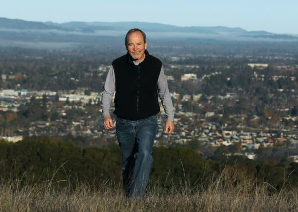 Supervisor Chris Coursey walking in a field on a hill with the City of Santa Rosa in the background