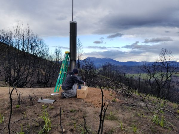 A man installs a 10-12 foot rainfall gauge on a burned hillside with charred trees.