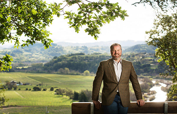 Supervisor James Gore standing by a bench with vineyard and green hills in the background.