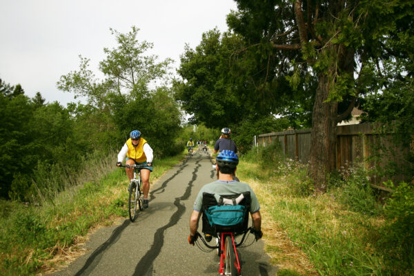 Two people on bikes, going in different directions on paved pathway.