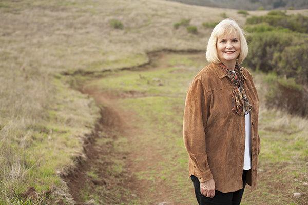 Supervisor Susan Gorin standing on a trail beside a golden field.